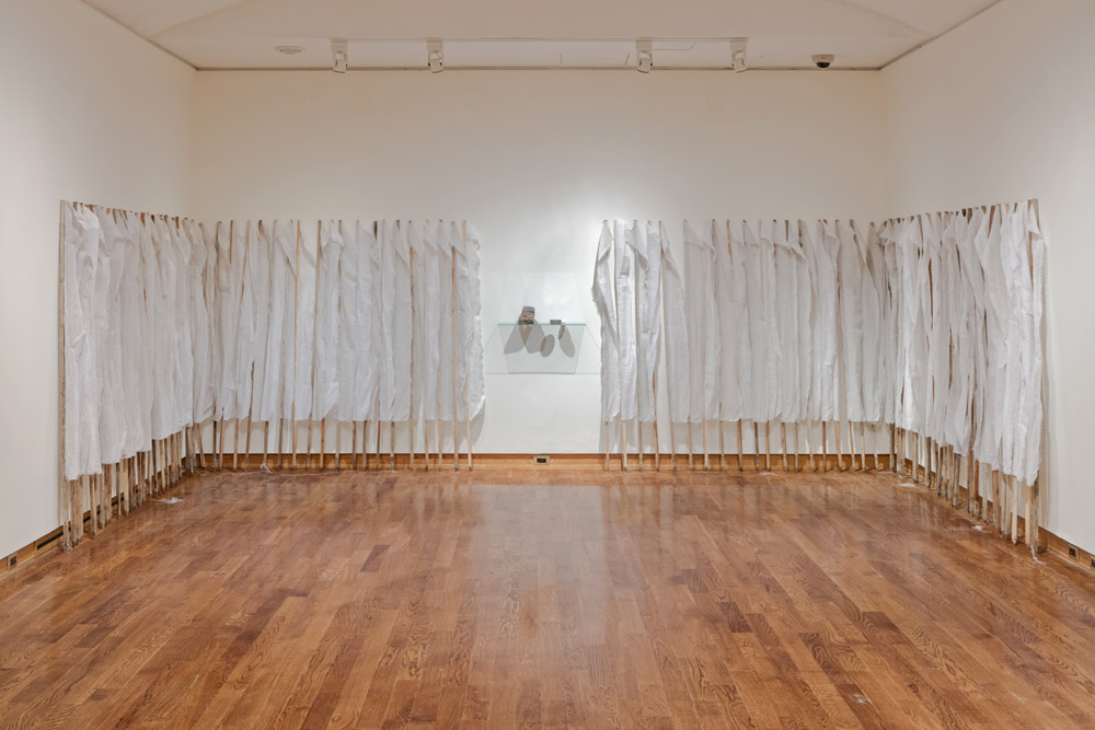 Installation shot of Phenomenology, 92 tall wooden stakes, each with a strip of white muslin attached to them, with a shelf sitting in the middle containing two indistinct objects