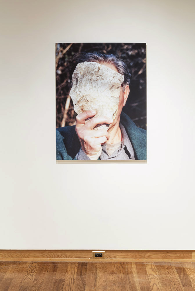 A man (the artist, Jimmie Durham) is holding a stone in front of his face, almost a perfect mirror of the shape of his head, it completely obscures his face.