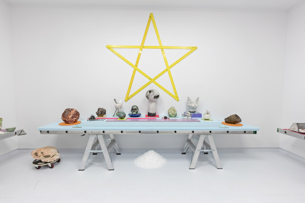 A white room filled with wican iconography, references to internet culture, rocks, crystals and raku skulls, computer mice, cat heads, and dildos