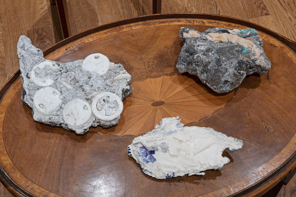 samples of greyish rocks with plastics of various plastics embeded inside them, sitting on two stately early twentieth century tables