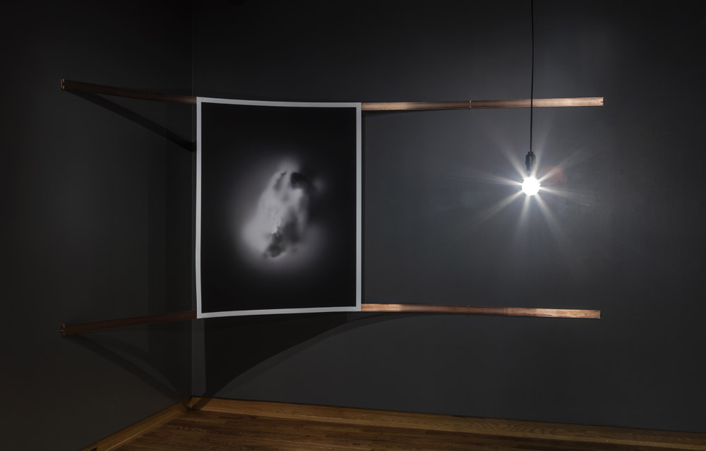 A ghostly radiogram of a rock, hung from two copper bars bent into a corner, lit by a bare LED bulb hanging from the ceiling