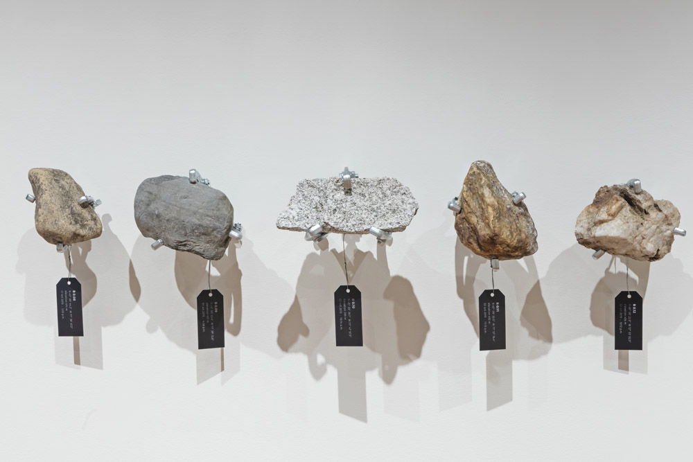rocks suspended in front of a wall, with black tags hanging from them with GPS co-ordinates