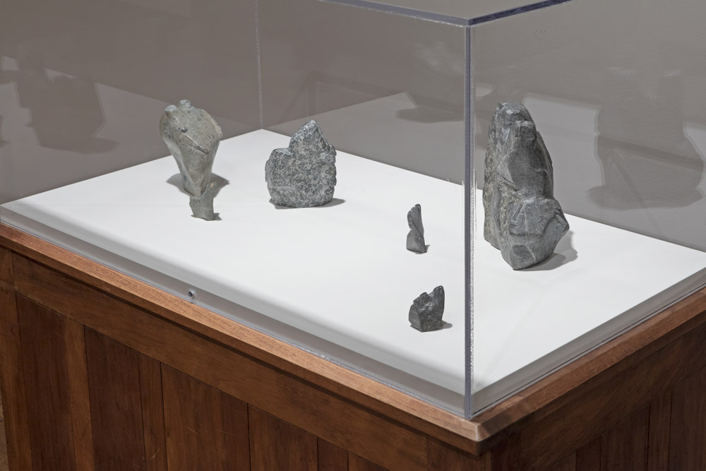 six rocks in a vitrine with subtle little faces carved into them