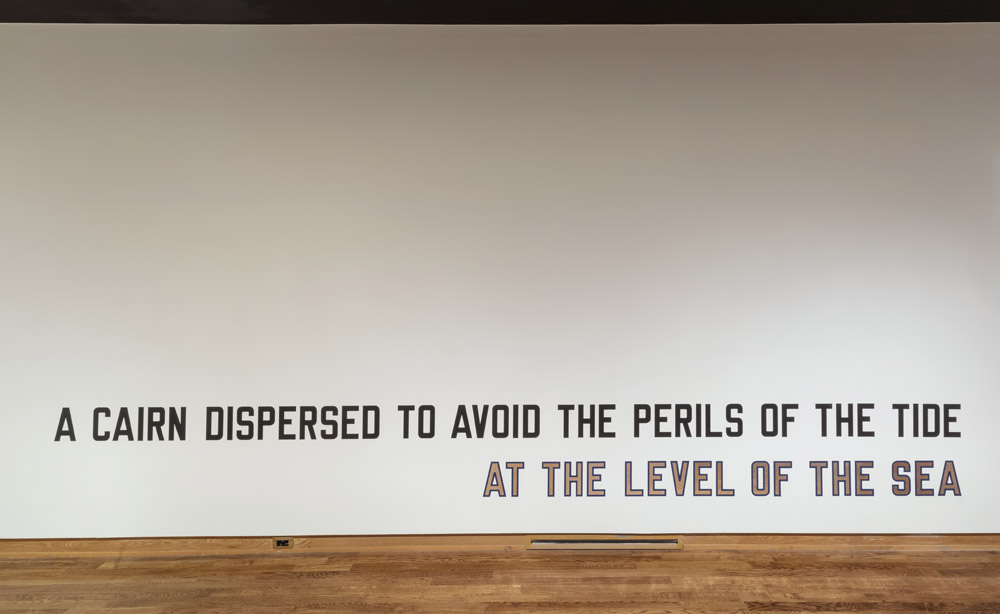 Image of the titular phrase installed as vinyl lettering on a gallery wall. All the vinyl is black except for the workds AT THE LEVEL OF THE SEA which are in mirror vinyl outlined with blue